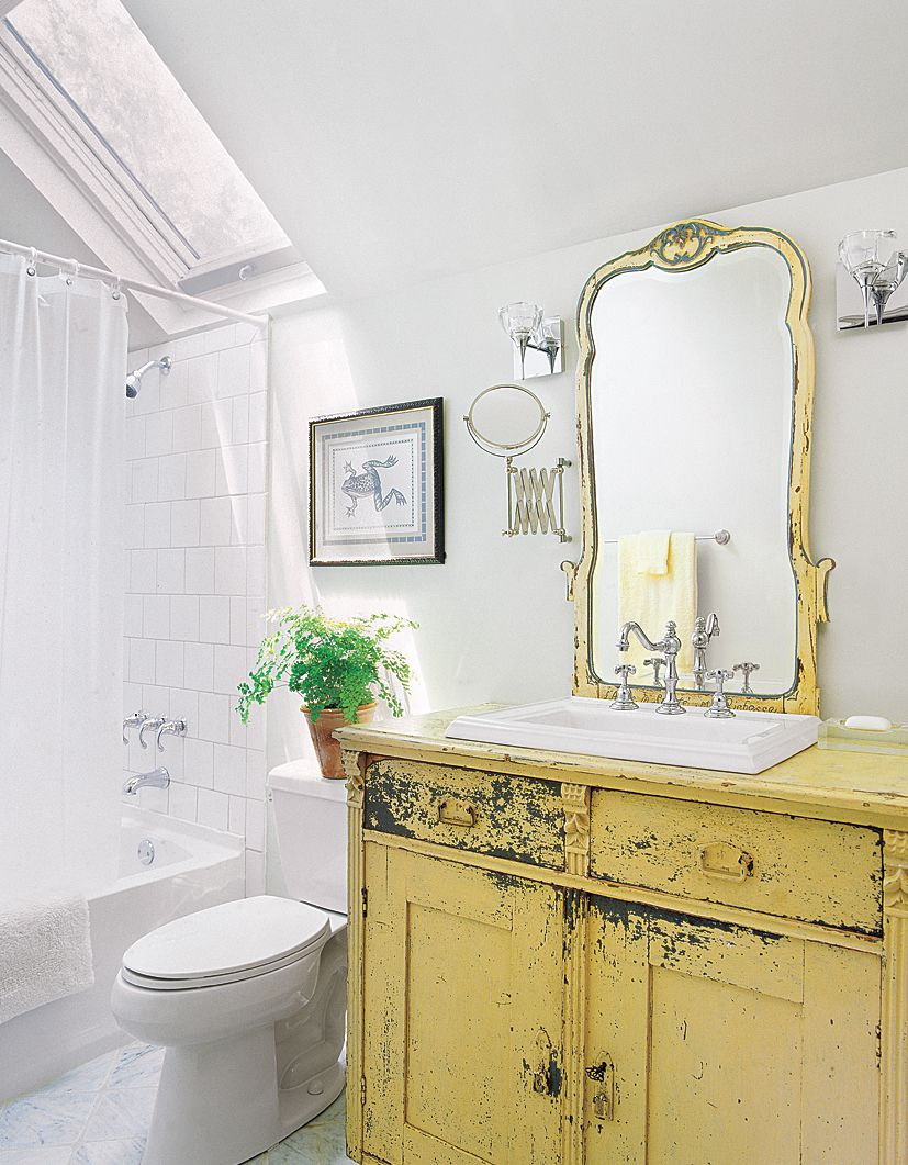 Yellow distressed vintage bathroom vanity and sink in an all white bathroom.