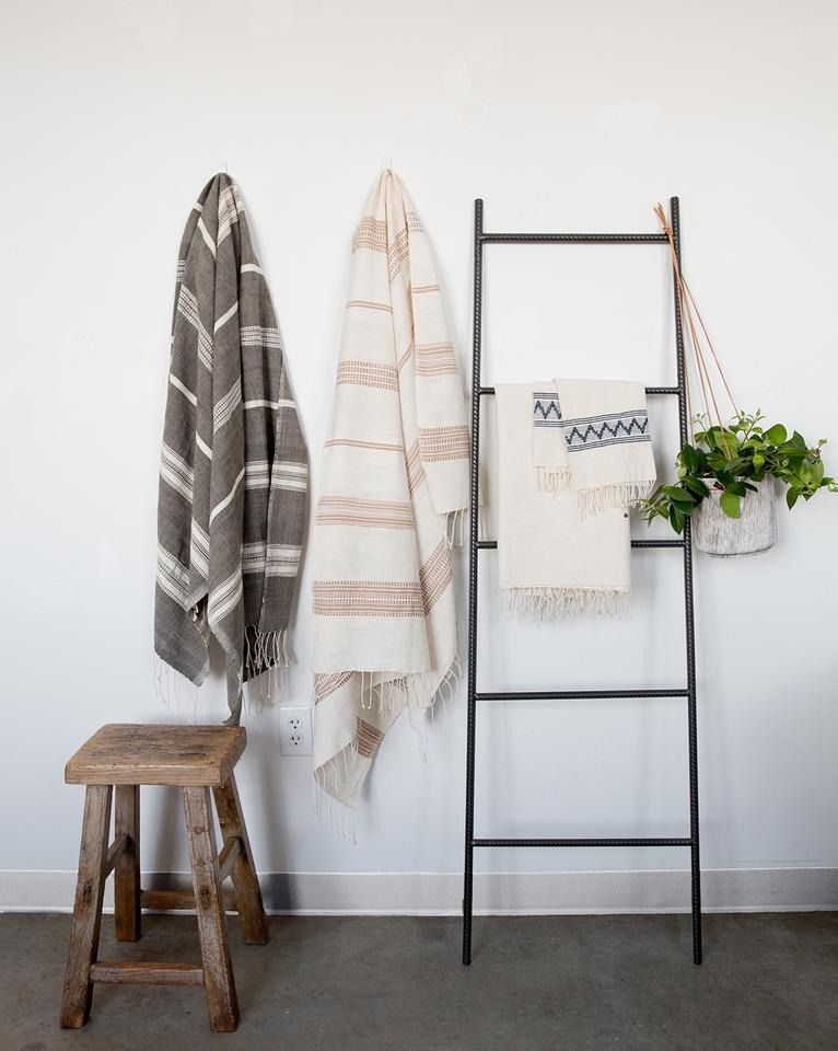 A black ladder leans against a wall, next to towels hanging on a hook.
