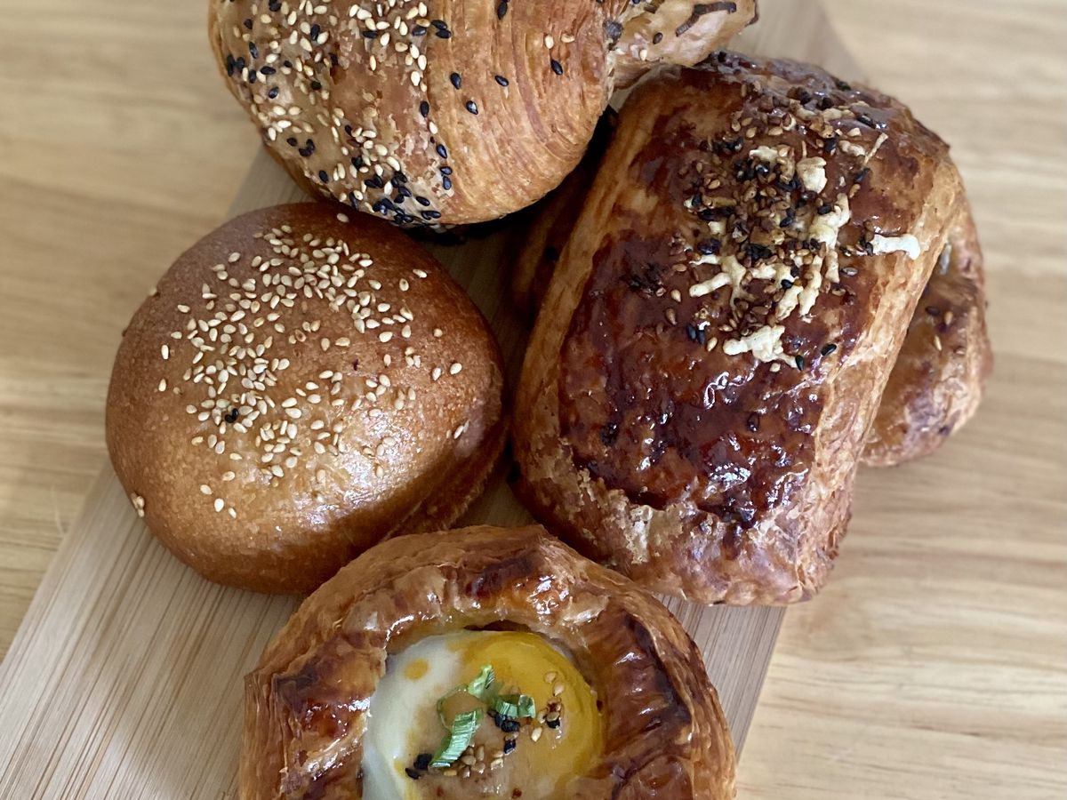 Four pastries on a wooden table including a Danish topped with an egg and a croissant covered in everything bagel seasoning.