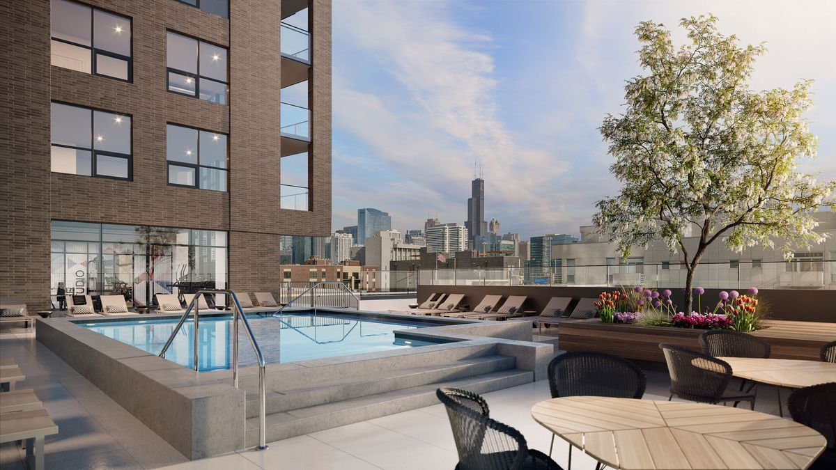 A rectangular pool surrounded by lounge chairs and tables and a leafy tree. The Chicago skyline can be seen in the distance. The attached brick tower climbs to the left.