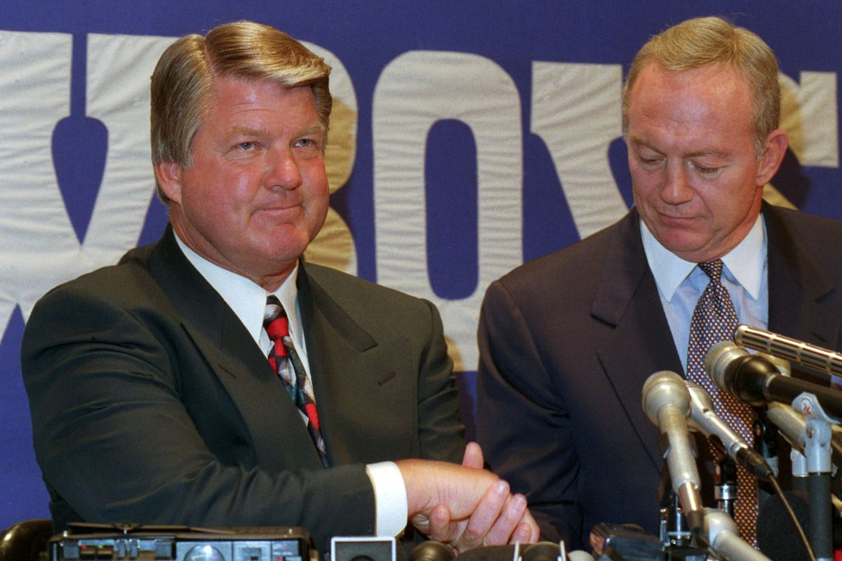 Jimmy Johnson, left, shakes hands with Dallas Cowboys owner Jerry Jones at a news conference in Irving, Texas, in 1994.