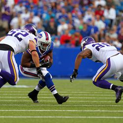 Aug 16, 2013; Orchard Park, NY, USA;  Minnesota Vikings outside linebacker Chad Greenway (52) and cornerback Chris Cook (20) look to make a tackle on Buffalo Bills running back C.J. Spiller (28) during the first half at Ralph Wilson Stadium.