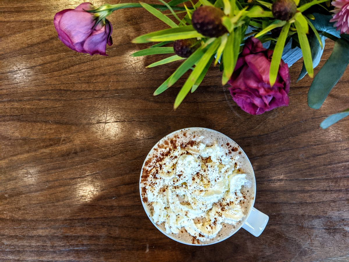 Overhead view of a white mug of hot chocolate on a wooden table There's whipped cream and cocoa powder on the hot chocolate. A bouquet of flours peek in from the top right corner of the photo.