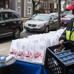 Aiden Carvajal, 6, watches from the car as his mom receives three days of free breakfast and lunch meals from lunchroom workers at William P. Nixon Elementary School, 2121 N. Keeler Ave., Thursday morning, March 19, 2020.