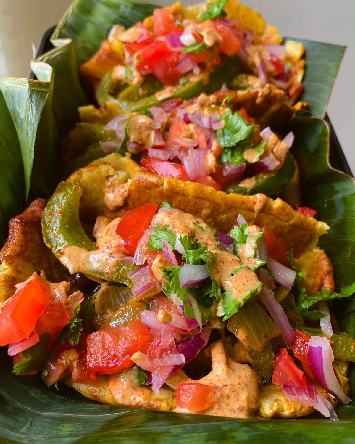 Three tacos filled with plantains, tomatoes, red onions, peppers, and green herbs drizzled in an orange sauce and laying on green banana leaves