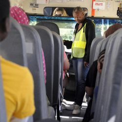 In this photo taken Aug. 18, 2012, Sharon Beal, center, a bus monitor in the district for 25 years, participates during a bus orientation open house for parents and students riding the bus for the first time this school year, at the Buffalo Academy for Visual and Performing Arts, in Buffalo, N.Y. The cell phone video of a bus monitor's cruel taunting, in June, ignited a global outpouring of support for the monitor and revulsion at her middle-school tormentors. The video raised questions about the role of bus monitors, including how much they can really do to protect against bullies while seeing riders safely on and off the bus, and how its victim, the bus monitor and supposed authority figure on the bus, could command so little respect.