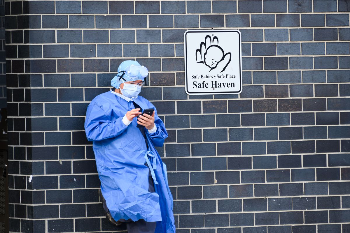 A person wearing protective equipment looks at a phone while leaning against a wall.