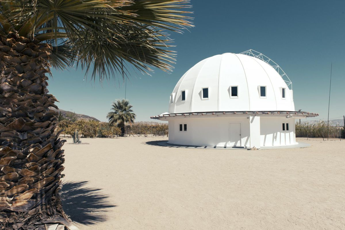 A white dome shaped building in a desert. There are palm trees.