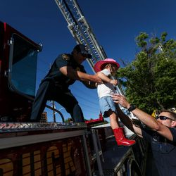 Firefighter Jake Blaskowski passes Kate Moore, 2, to firefighter Brandon Heaney while the Salt Lake City Fire Department shows off its two new ladder trucks at Smith's Ballpark in Salt Lake City on Tuesday, June 27, 2017.