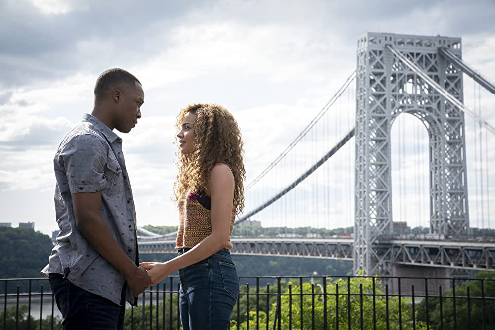 A young man and a woman stand, holding hands, with the George Washington Bridge in the background.