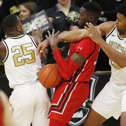 Utah center Lahat Thioune, center, fights for control of a rebound with Colorado guard McKinley Wright IV, left, and forward Evan Battey in the second half of an NCAA college basketball game Sunday, Jan. 12, 2020, in Boulder, Colo.
