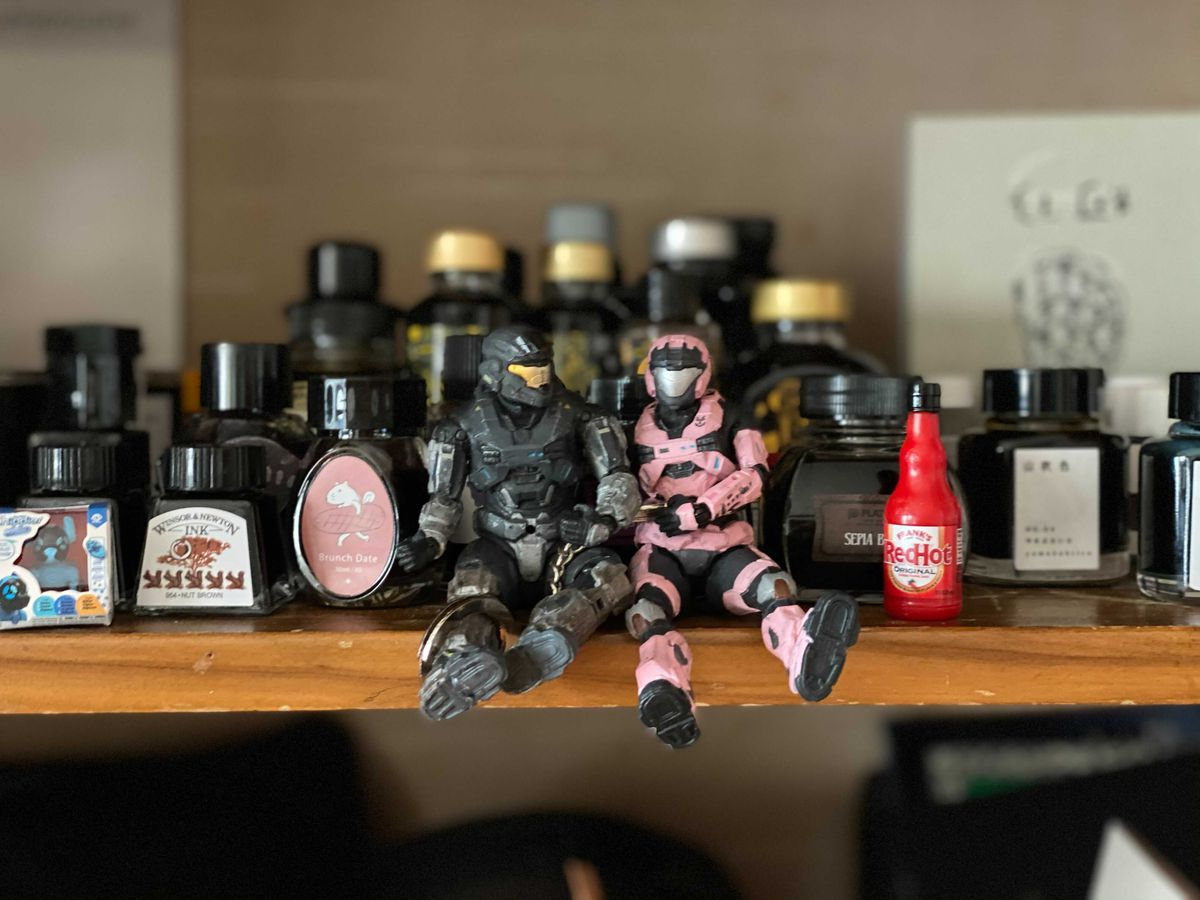 Two Spartan action figures from Halo Reached sitting on a shelf, handcuffed together.