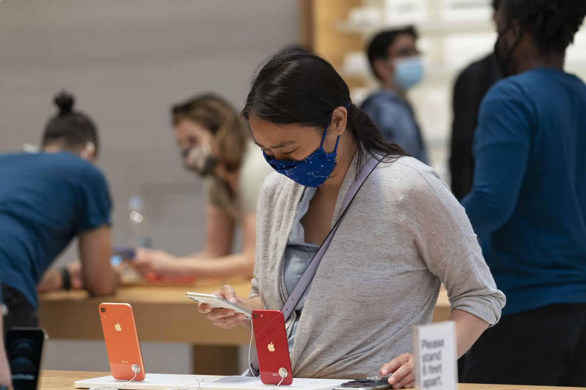 A customer looks at the iPhone 12 in an Apple store on Friday, May 21, 2021, in New York.