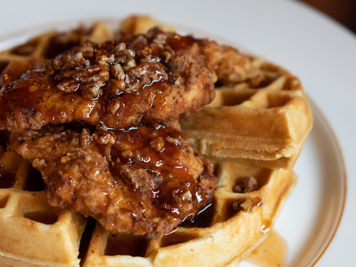 Broussard's chicken and waffles with glazed chicken, buttermilk waffles, maple syrup, candied pecans, and whipped butter