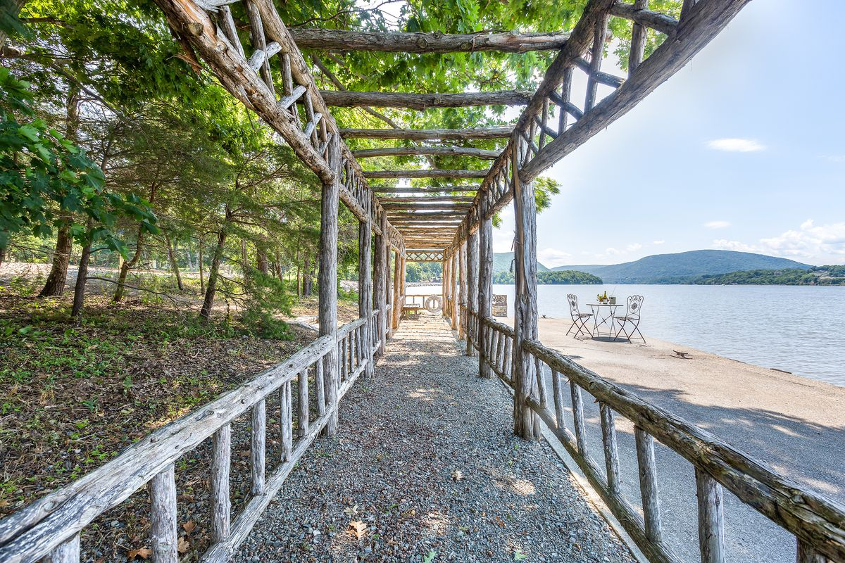 A dock sits on adjacent to a stretch of beach on the river. The dock features a pergola style roof.