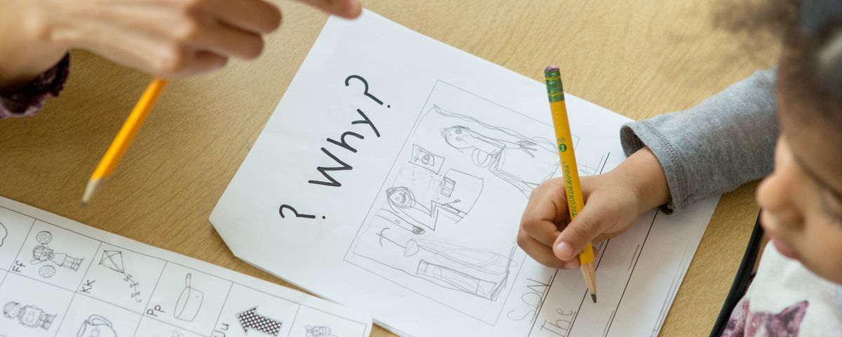 """A teacher points to a kindergartener's paper as she writes on it with a pencil. At the top of the worksheet, the word """"Why?"""" is in bold black letters."""