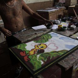 In this Sept. 1, 2012 photo, an inmate belonging to the Mara 18 gang works on a painting inside the prison in Cojutepeque, El Salvador.  Six months after El Salvador brokered an historic truce between two rival gangs to curb the nation's daunting homicide rate, officials are split over whether the truce actually works. The gangs, which also operate in Guatemala and Honduras, are seeking truce talks in those countries as well.