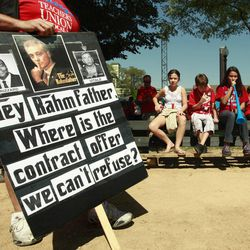 """A protester holds a sign critical of Chicago mayor Rahm Emanuel during a rally of striking Chicago school teachers Saturday, Sept. 15, 2012, in Chicago. Union president Karen Lewis reminded the crowd that although there is a """"framework"""" for an end to their strike, they still are on strike."""