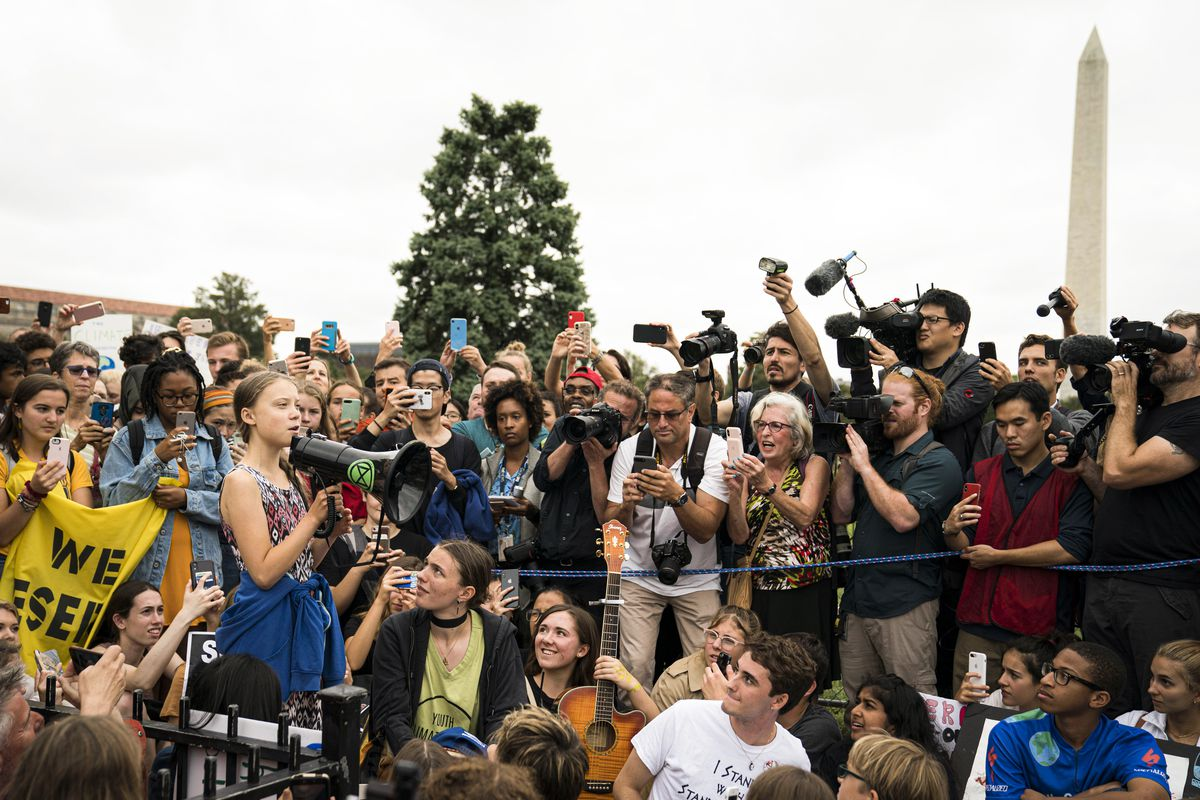 Swedish climate activist Greta Thunberg speaks into a bullhorn whiles surrounded by other student environmental advocates.