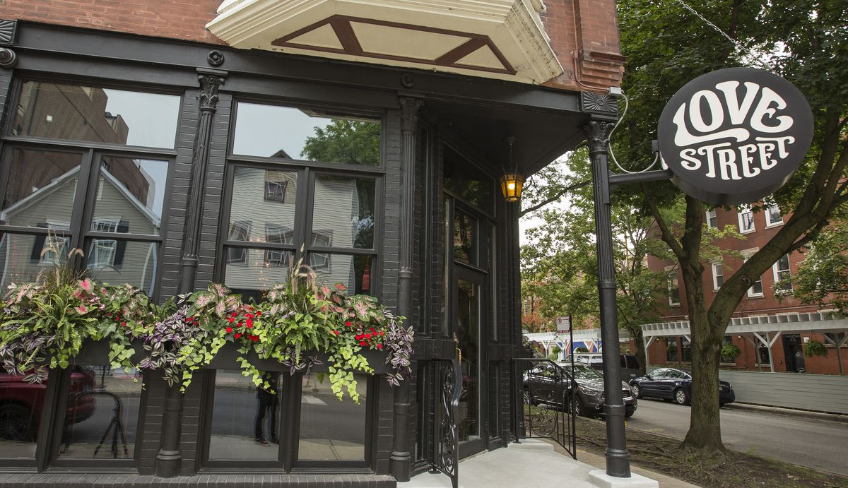 A bar storefront with hanging planters.