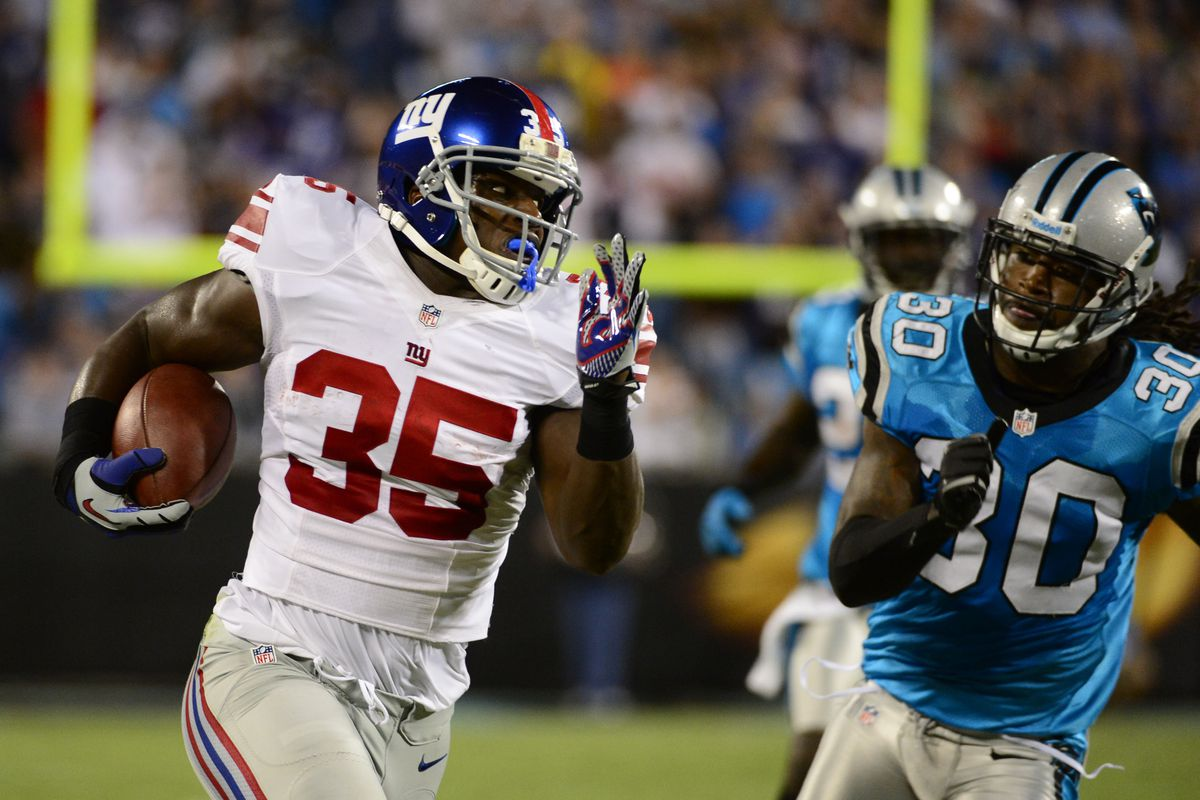 Sep 20, 2012; Charlotte, NC, USA; New York Giants running back Andre Brown (35) runs as Carolina Panthers strong safety Charles Godfrey (30) defends during the first quarter at Bank of America Stadium.  Bob Donnan-US PRESSWIRE