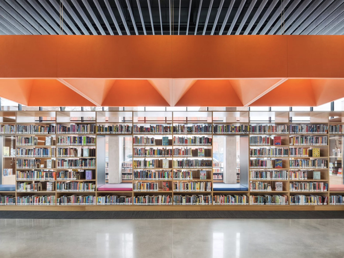 Stacks of shelves in a bright, modern-looking space under an orange ceiling.