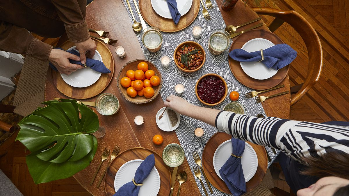 Overhead view of a table set for dinner, a wooden table with a blue and white runner, 5 dinner plates set with navy blue napkins in napkin rings, and brass flatware. There are bowls of snacks as well as a bowl of clementines. There are also plants.