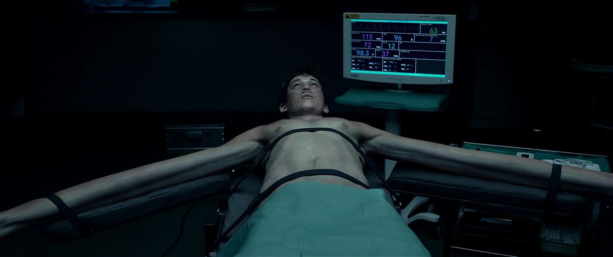 Miles Teller lying on a surgical bed with his arms stretched out in Fantastic Four 2015