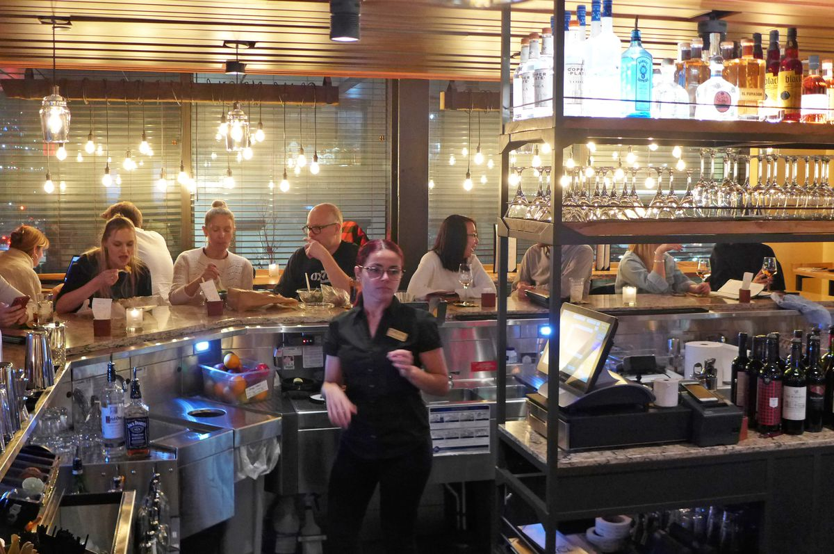 A bar with a line of drinkers and a bartender standing in front.