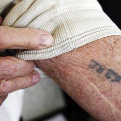 Holocaust survivor Abe Katz shows his prison camp markings after a Utah Holocaust Memorial Commemoration at the Jewish Community Center in Salt Lake City, Thursday, April 19, 2012.