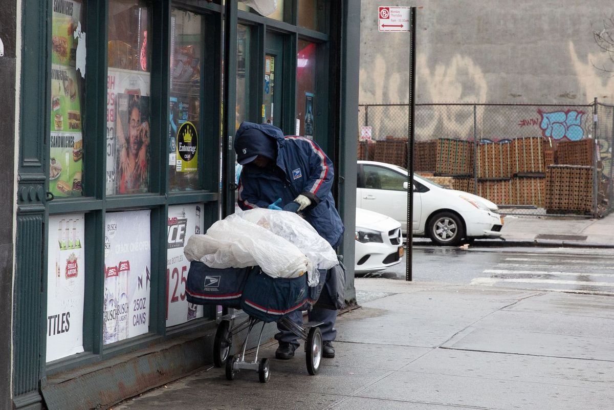A Brooklyn postal worker takes precautions during the coronavirus outbreak.