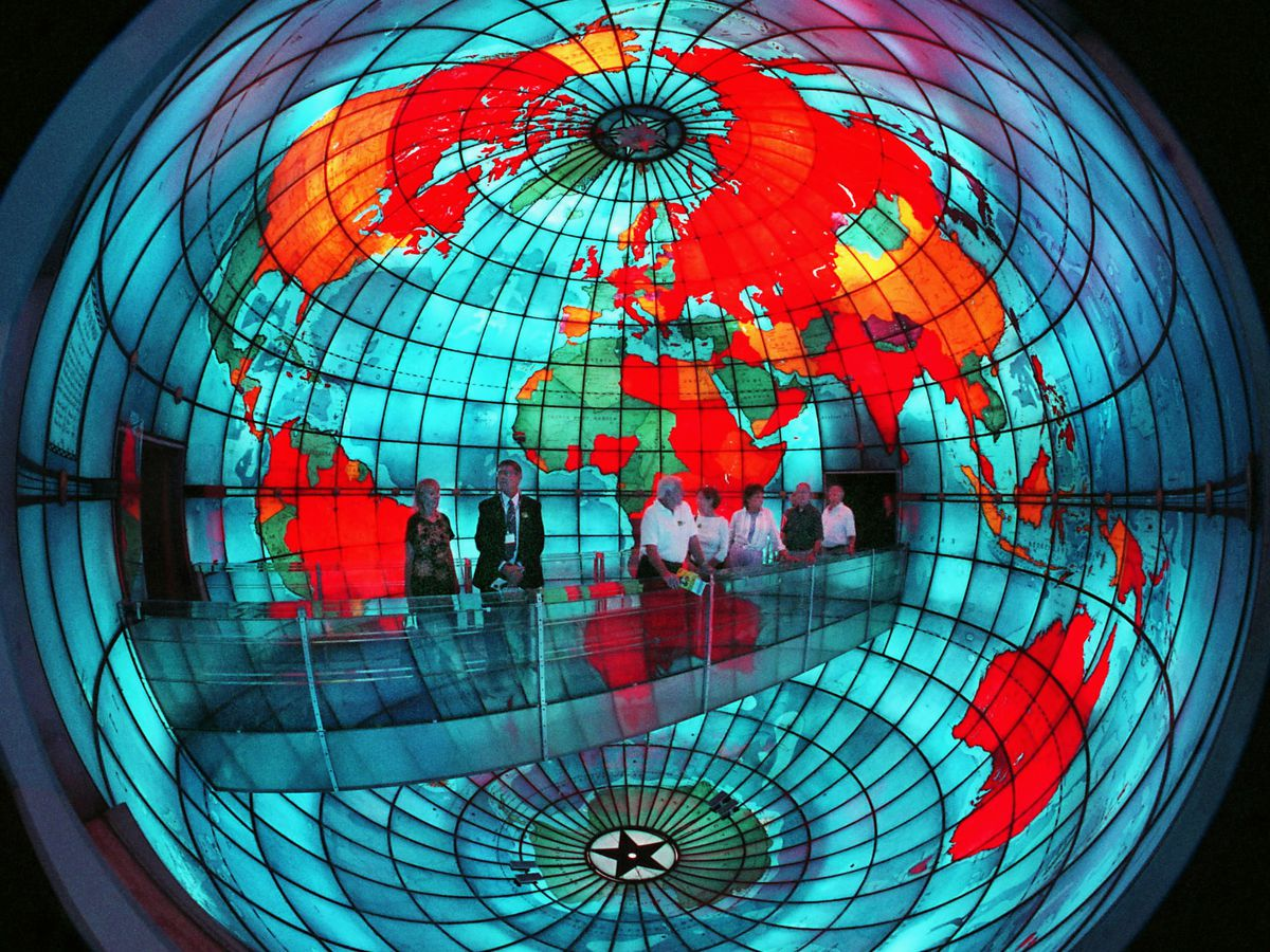 A large colorful glass globe. There are people standing at a desk area within the globe.