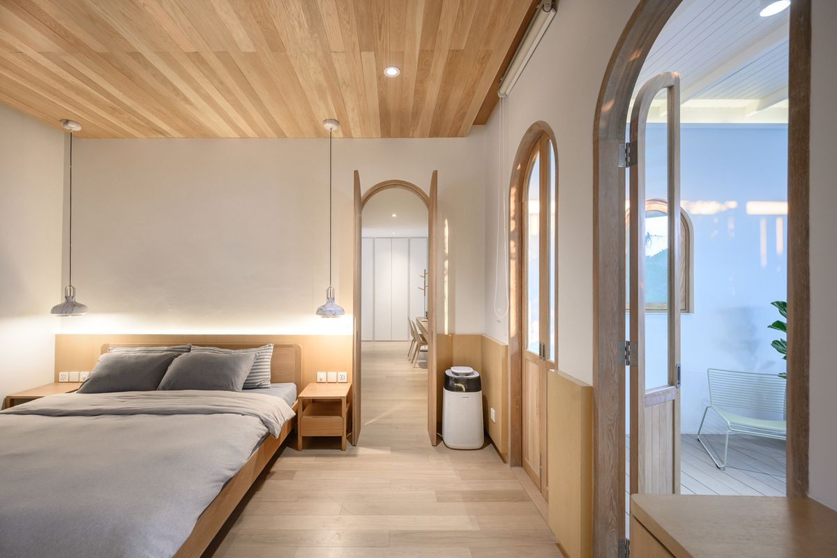 Bedroom with wooden ceiling, floors, and platform bed.