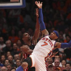 New York Knicks' Carmelo Anthony, right, tries to make a shot past Miami Heat's Chris Bosh, left, and is fouled by LeBron James in the first half of the NBA basketball game in New York, Sunday, April 15, 2012.