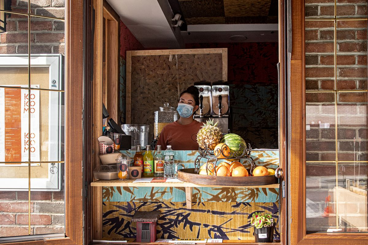 A person stands behind a restaurant takeout window with drinks and fruit set up on a counter
