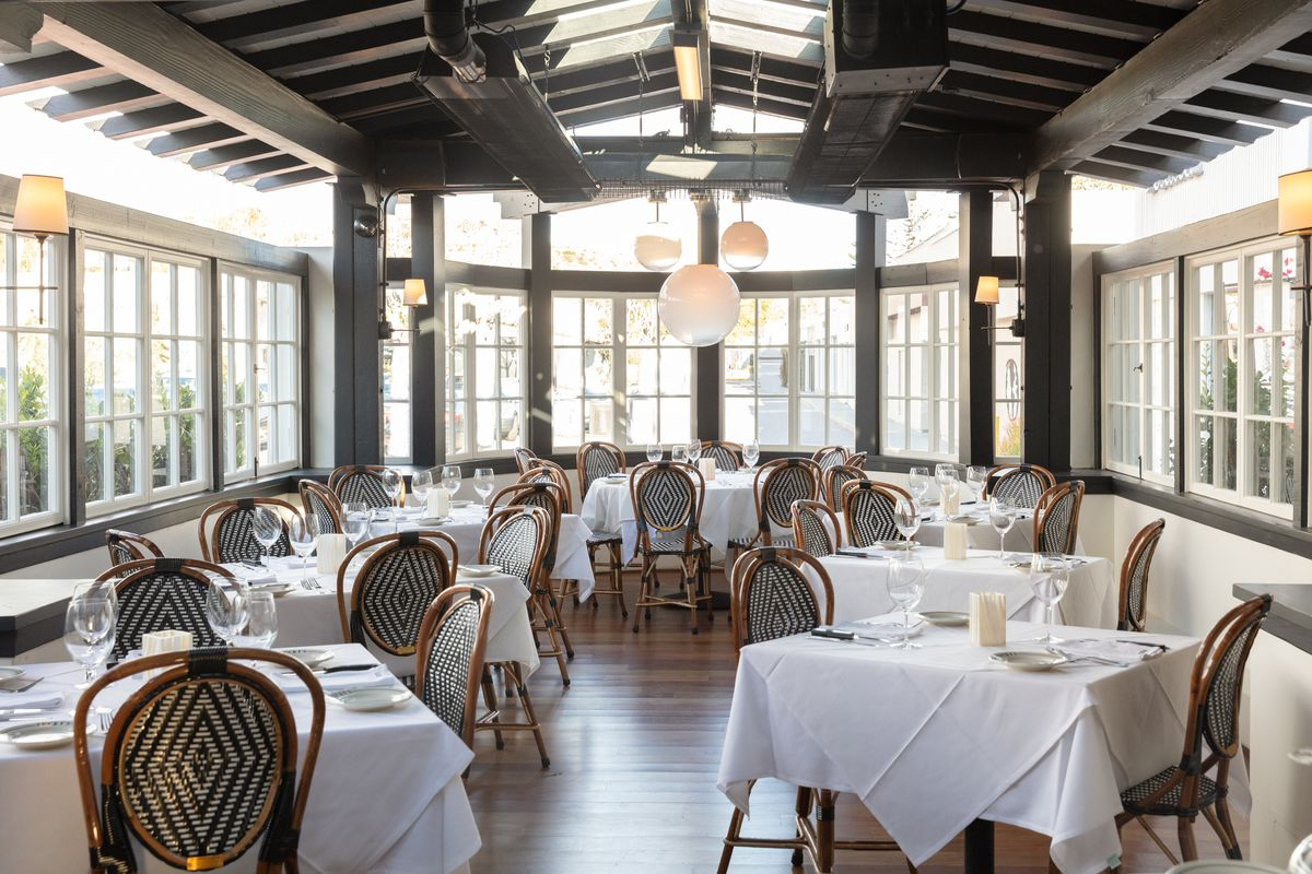 A long room with lots of sunlight from wraparound windows, featuring white tablecloth tables.