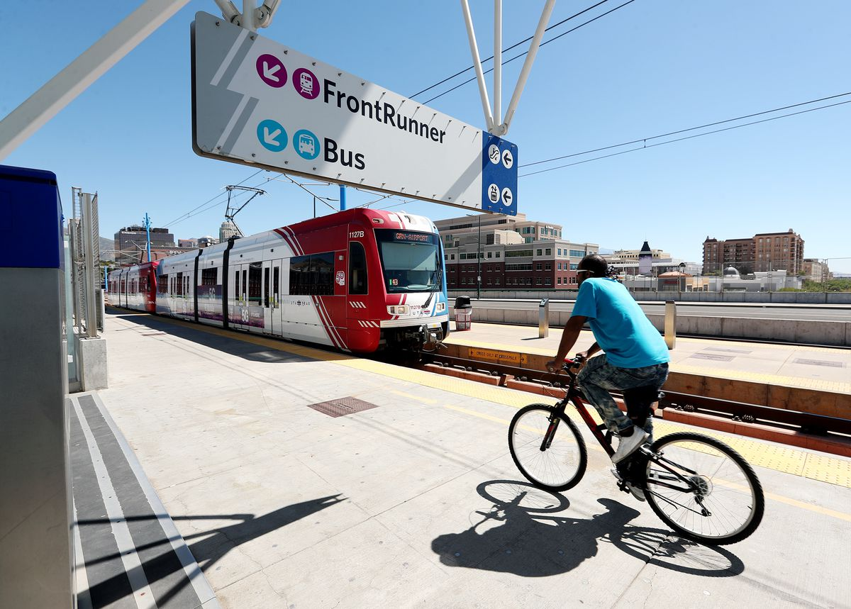 A TRAX light-rail train pulls into the North Temple Bridge/Guadalupe Station in Salt Lake City as a cyclist rides past on Tuesday, Sept. 1, 2020.