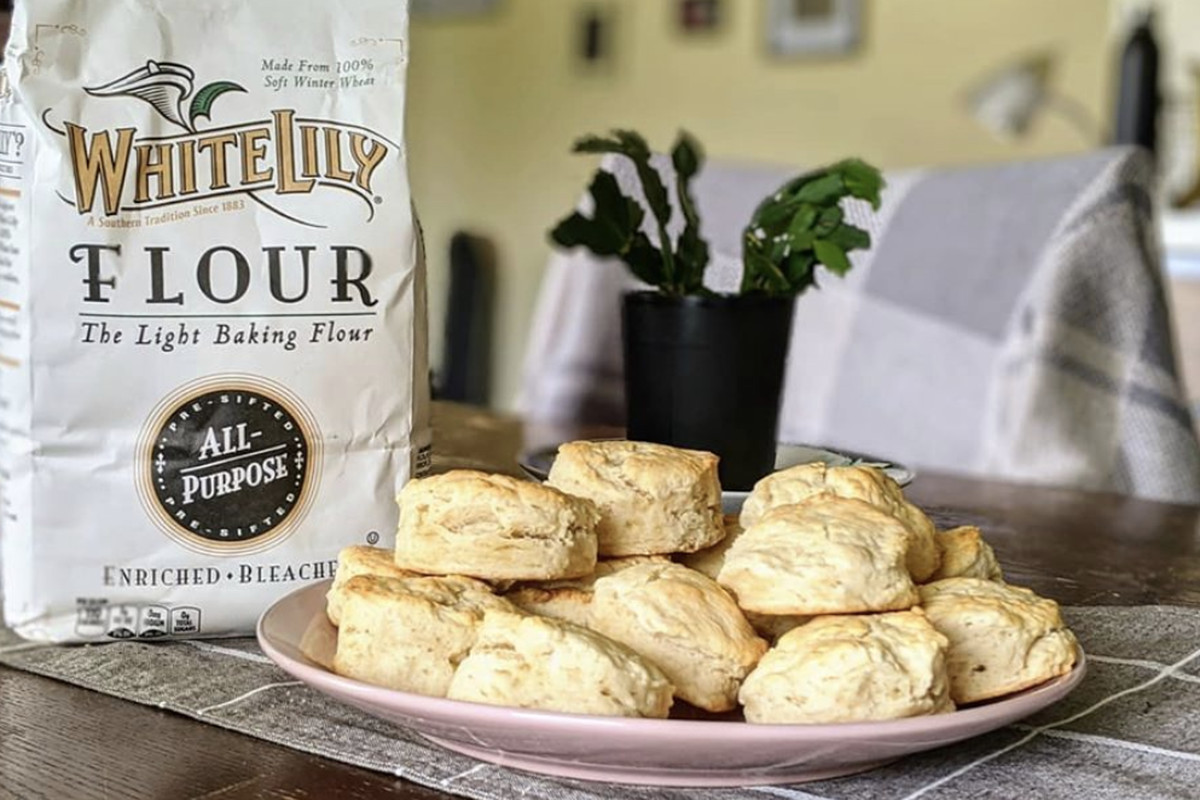 A bag of White Lily flour sits next to a plate of biscuits.