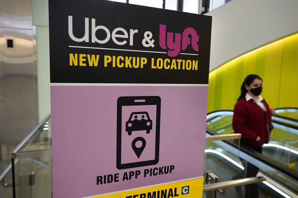 In this Feb. 9, 2021 file photo, a passer-by walks past a sign offering directions to an Uber and Lyft ride pickup location at Logan International Airport, in Boston.