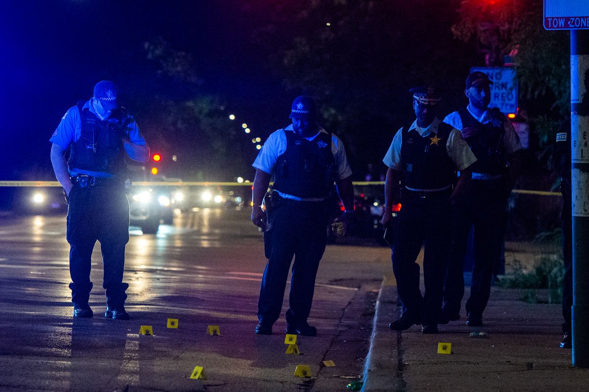 Police place evidence markers on the street at the scene of a shooting.
