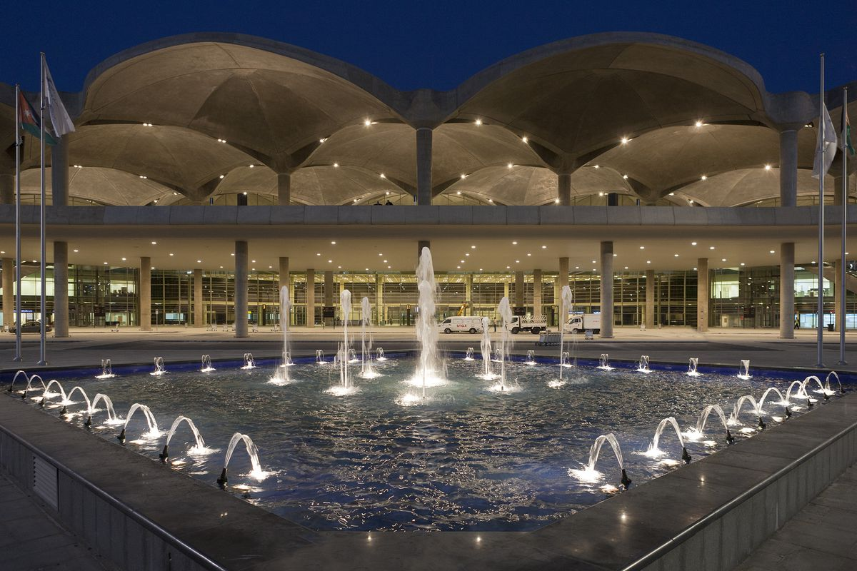 The exterior of the Queen Alia International Airport in Jordan. The roof is comprised of concrete domes. There are columns. In the foreground is a fountain.