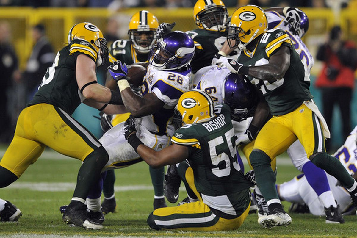 GREEN BAY WI - OCTOBER 24:  Adrian Peterson #28 of the Minnesota Vikings is stopped by Desmond Bishop #55 of the Green Bay Packers at Lambeau Field on October 24 2010 in Green Bay Wisconsin. (Photo by Jim Prisching/Getty Images)