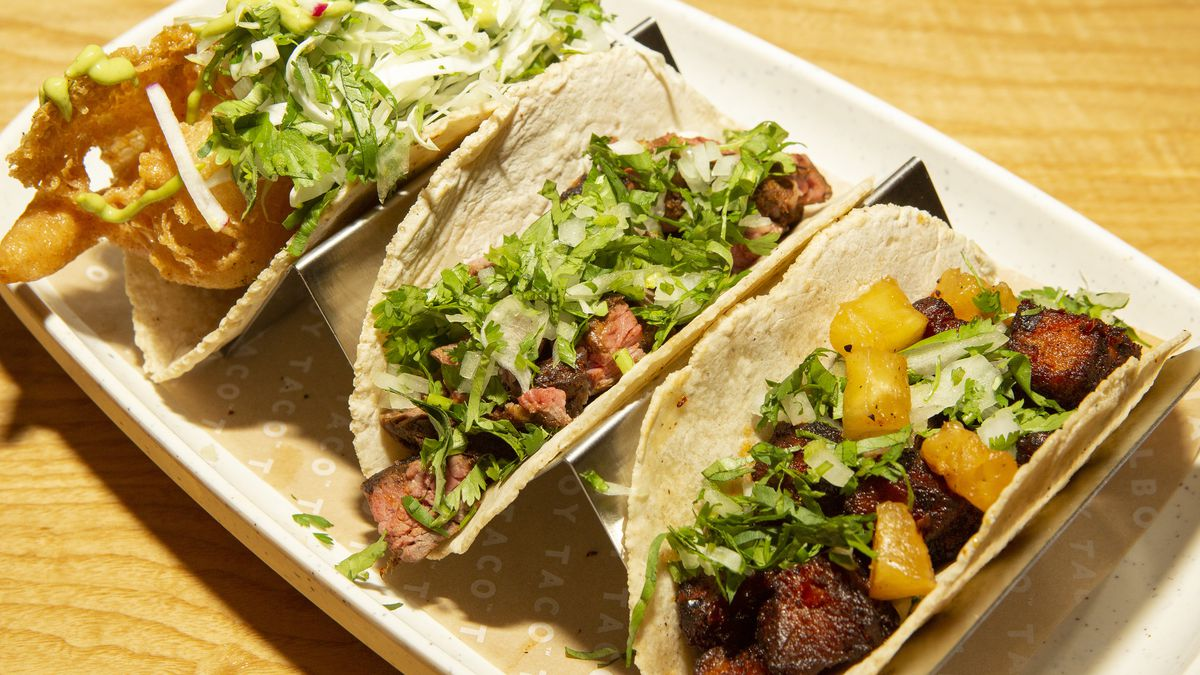 Three tacos in corn tortillas lined up on a plate