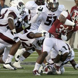 Arkansas running back Dennis Johnson (33) pushes past Louisiana Monroe linebacker R.J. Young (51), Louisiana Monroe's Conner Fryoux, bottom right, safety Isaiah Newsome, center, and safety Mitch Lane, left, during the second quarter of an NCAA college football game in Little Rock, Ark., Saturday, Sept. 8, 2012.