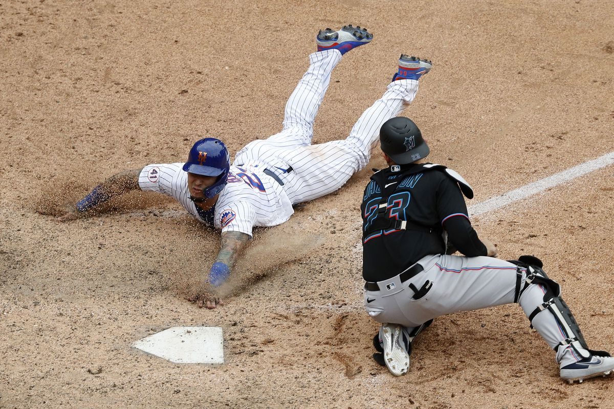 Javier Baez #23 of the New York Mets slides home with the game winning run in the ninth inning against Alex Jackson #23 of the Miami Marlins at Citi Field