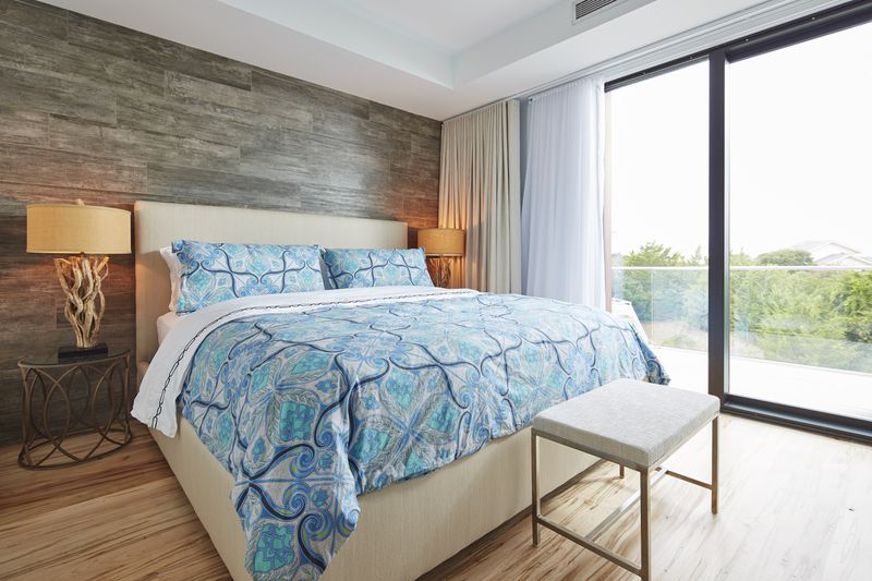 A bbed with a teal patterned comforter and cream headboard sits on wooden floors. A sliding glass door opens out to a second story balcony.