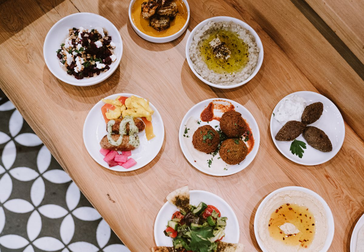 A colorful mezze spread on a light wooden table