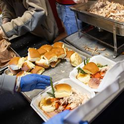 Volunteers prepare hot meals to be distributed at the Rescue Mission of Salt Lake in Salt Lake City on Saturday, Dec. 19, 2020. Volunteers handed out hot meals as well as hundreds of pairs of boots to people experiencing homelessness.