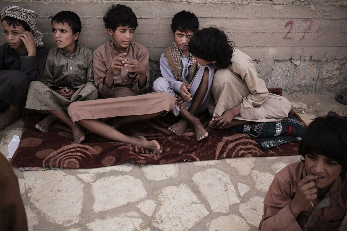 July 27: Abdel Hamid,14, second right, and Morsal, 14,third right, sit at a camp for displaced persons where they took shelter, in Marib, Yemen. Both boys were child solders forcibly enlisted by Houthi rebels and put to work carrying ammunition and suppli