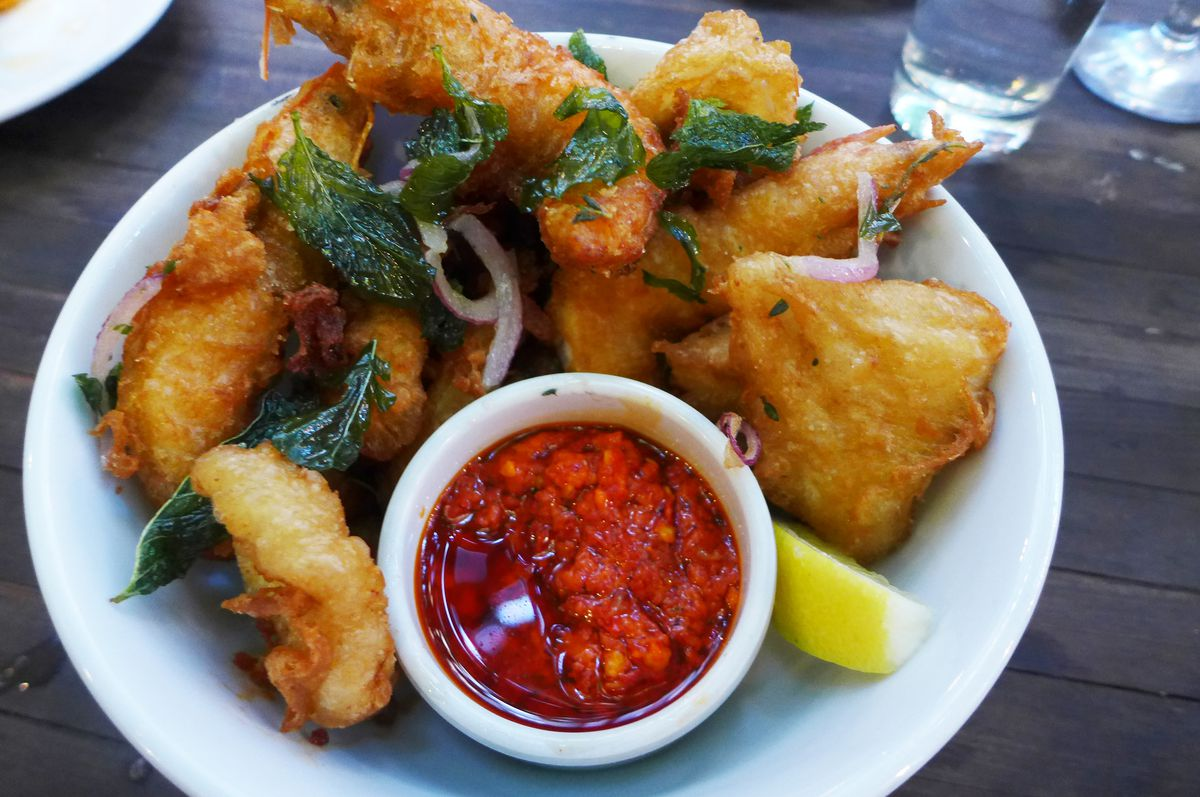 A heap of brown fried seafood with a bright red sauce.